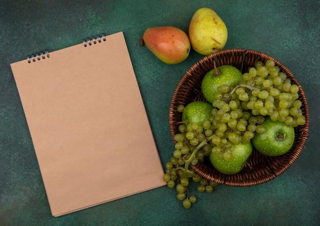 Top view copy space blocco note beige con uva verde e mele in un cesto di pere su uno sfondo verde
