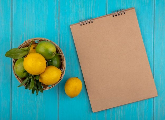 Top view copy space blocco note beige con limoni e limette in un cesto su uno sfondo turchese