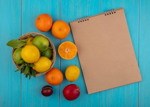 Top view copy space beige blocco note con sapels limoni e limette in un cesto su uno sfondo turchese