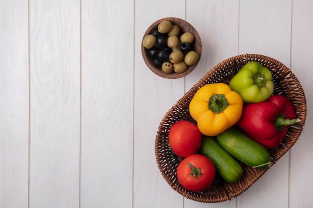 Top view copy space peperoni con pomodori cetrioli in un cesto con olive su uno sfondo bianco
