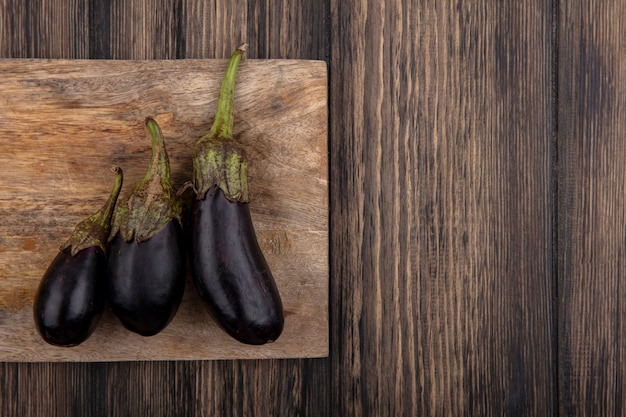 Top view  copy space black eggplant on cutting board on wooden background