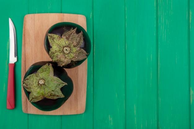 Вид сверху копией космического черного баклажана с ножом на разделочной доске на зеленом фоне