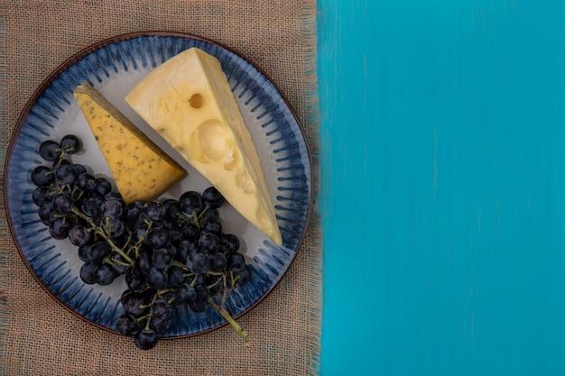 청록색 배경에 베이지 색 냅킨에 접시에 치즈 조각과 상위 뷰 복사 공간 검은 포도
