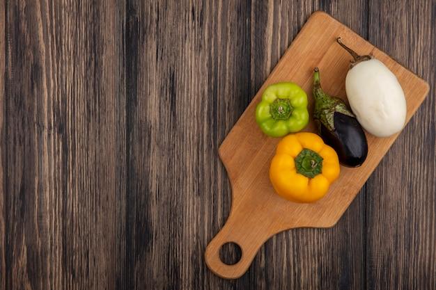 Vista dall'alto lo spazio della copia melanzane in bianco e nero con peperoni colorati sul tagliere su fondo di legno