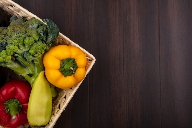 Вид сверху копией космической брокколи с болгарским перцем в корзине на деревянном фоне