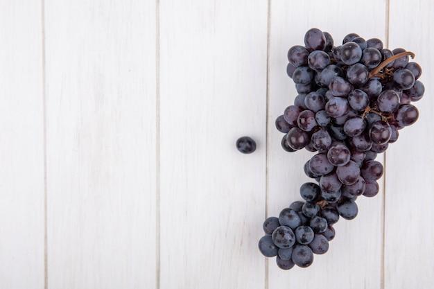 Vista dall'alto copia spazio mazzo di uva nera su sfondo bianco