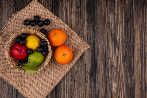 木製の背景にオレンジのバスケットにレモンライムと桃とトップビューコピースペースチェリープラム