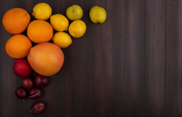 Vista dall'alto copia spazio ciliegia prugna con limoni arance pompelmo e pesca su fondo in legno