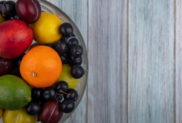 Vista dall'alto copia spazio ciliegia prugna con arancia limone e calce in vaso di frutta su sfondo grigio