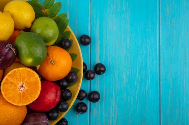 ターコイズブルーの背景の黄色いプレートにオレンジ、プラム、レモン、ライムのトップビューコピースペースチェリープラム