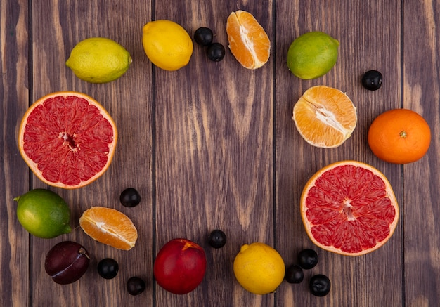Top view  copy space cherry plum with peach  lemons  limes  orange and half grapefruit on wood background
