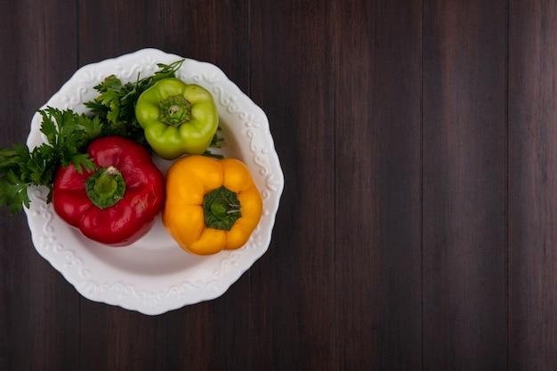 Vista dall'alto copia spazio peperoni colorati nel piatto con prezzemolo su fondo in legno