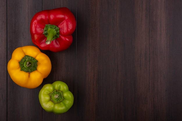 Top view  copy space colored bell peppers red  yellow and green on wooden background