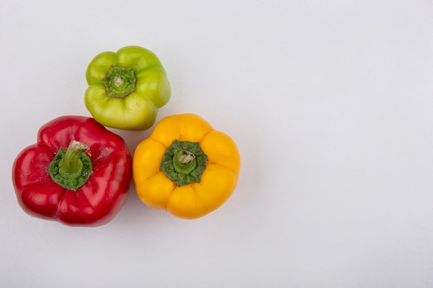 Top view  copy space colored bell peppers on white background