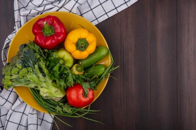 Top view copy space peperoni colorati con broccoli cetriolo pomodoro e cipolla verde sulla zolla gialla su fondo di legno