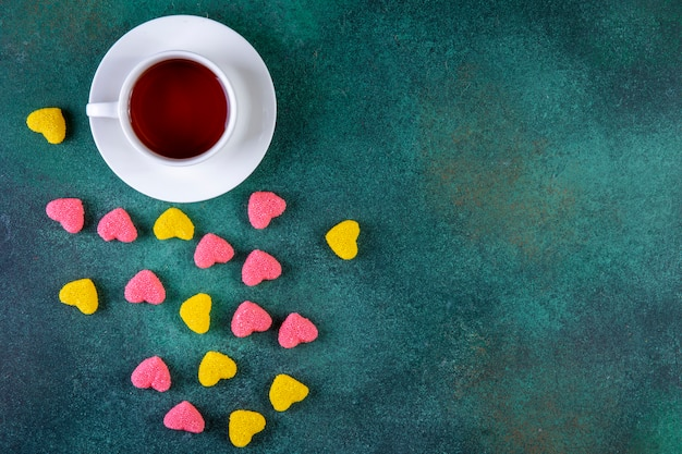 Top view copy space colored marmalade in the form of a heart with a cup of tea on green
