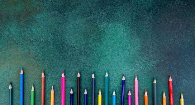 Top view copy space colorful pencils on a green background