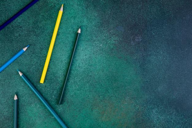 Вид сверху копией пространства красочных карандашей на зеленом фоне