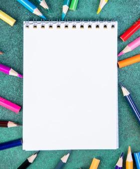 녹색 배경에 메모장 상위 뷰 복사 공간 다채로운 연필