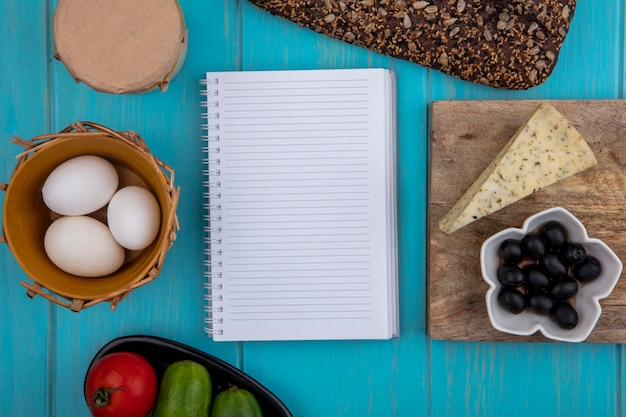 Top view  copy space copybook with black bread  cheese  olives  chicken eggs  yogurt and cucumbers with tomato on a turquoise background