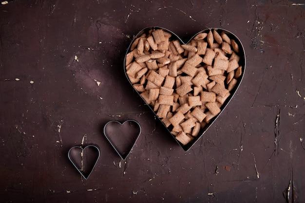 Vista dall'alto copia spazio? corn flakes a forma di cuore su uno sfondo marrone