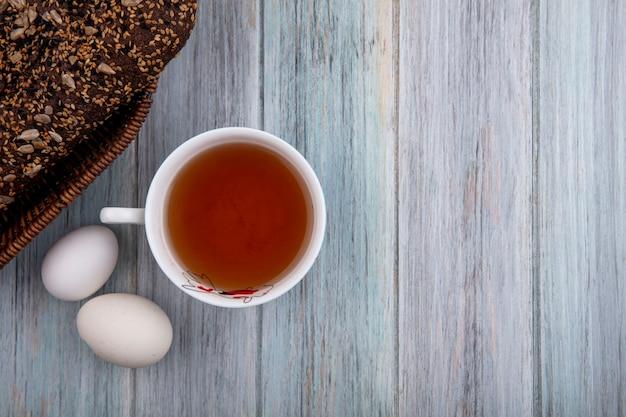 Vista dall'alto copia spazio tazza di tè con uova di gallina e pane nero su sfondo grigio