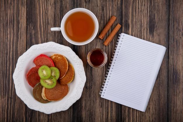 Vista dall'alto copia spazio tazza di tè con frittelle e fette di kiwi su un piatto con blocco note e cannella su fondo in legno