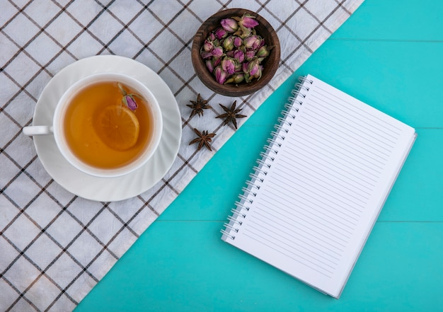 Top view copy space cup of tea with a slice of lemon and a notebook with dried flowers on a light blue background