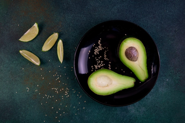 Top view copy space cut in half avocado on a plate with sesame seeds and lemon on a dark green background