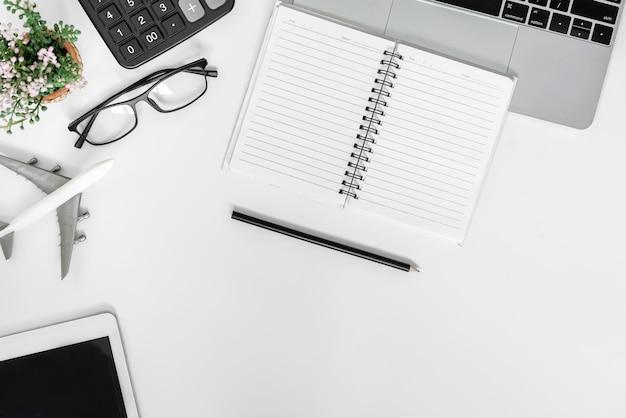 上面図のコピースペース。ノートパソコン、木製のテーブルに空白のメモ帳を備えたデスクオフィス。