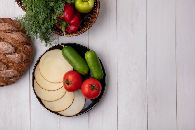 白い背景の上のスモークチーズトマトとキュウリのバスケットにピーマンとトップビューコピースペースディル