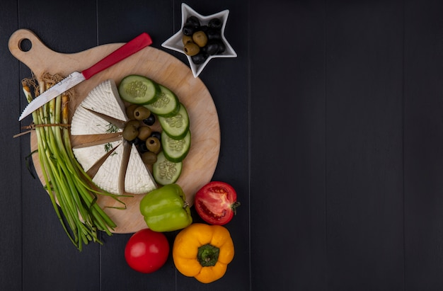 Top view  copy space feta cheese with olives  cucumber  green onions  bell peppers with a knife on a stand  on a black background