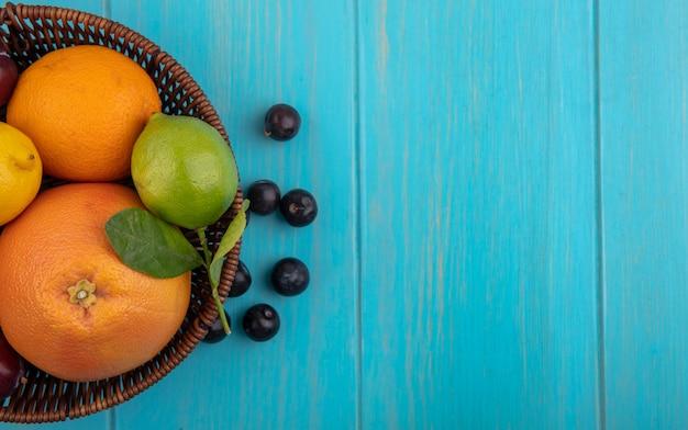 Vista dall'alto spazio copia mix di frutta in un cesto di pompelmo arance limoni limette e prugne ciliegia su uno sfondo turchese