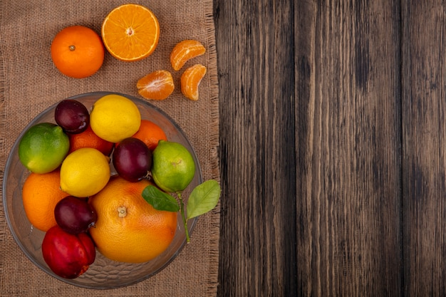 Top view  copy space fruit mix lemons  limes  plum  peach and orange in a vase on a beige napkin  on a wooden background