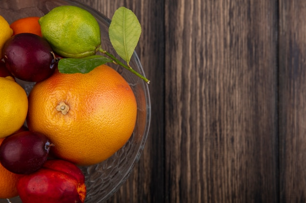 Top view  copy space fruit mix lemons  limes  plums  peaches and oranges in a vase on a wooden background
