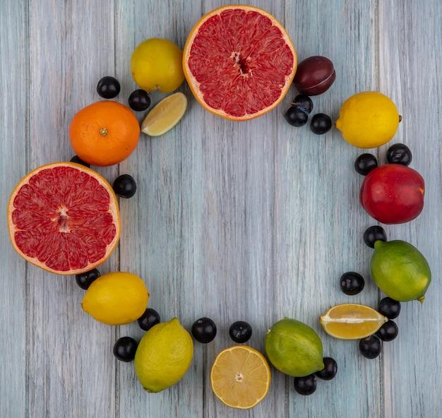 Top view  copy space grapefruit halves with cherry plum  orange  peach  plum  lemon and lime on gray background