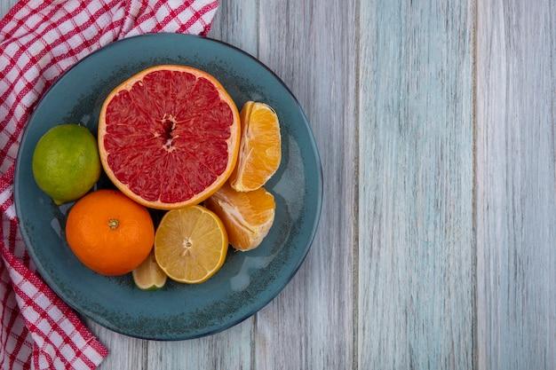 Top view copy space metà pompelmo con arancia e limone con calce su un piatto su un asciugamano a scacchi su uno sfondo grigio