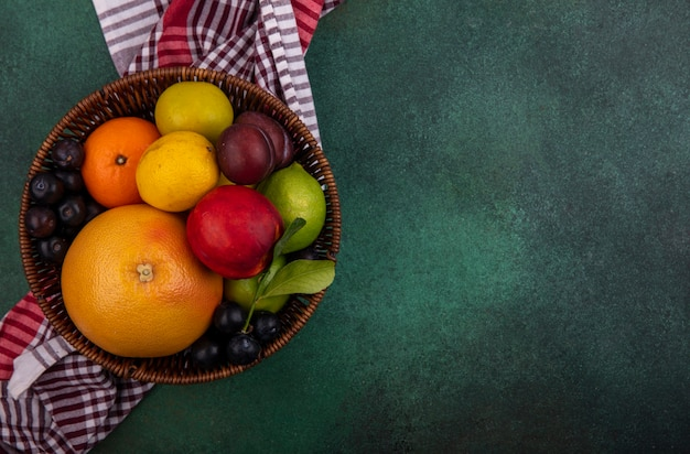 Top view  copy space grapefruit with lime  lemon  peach  cherry plum  orange and plum in a basket on a green background