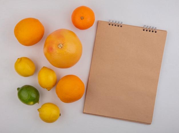 Вид сверху копией космического грейпфрута с апельсинами и лимонами с блокнотом на белом фоне