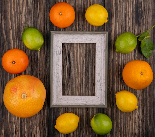 Top view  copy space grapefruit with oranges  lemon  limes and gray frame on wooden background