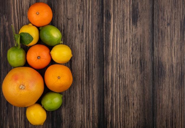 Vista dall'alto copia spazio pompelmo con arance limoni e limette su fondo in legno