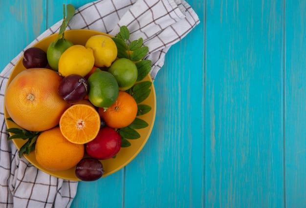 Vista dall'alto spazio copia pompelmo con arance prugne limoni e limette su una piastra gialla su un asciugamano a scacchi su uno sfondo turchese