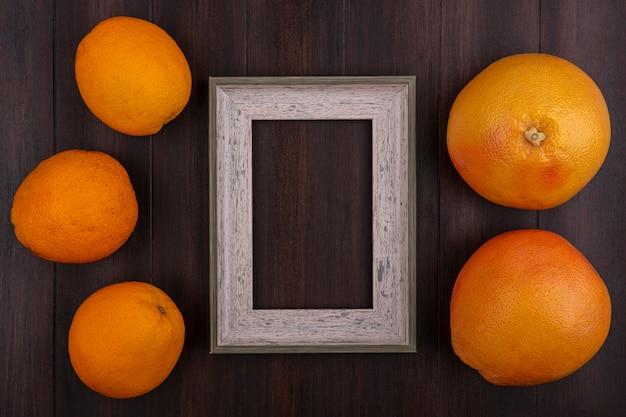 Vista dall'alto lo spazio della copia pompelmi con arance e cornice grigia su fondo in legno