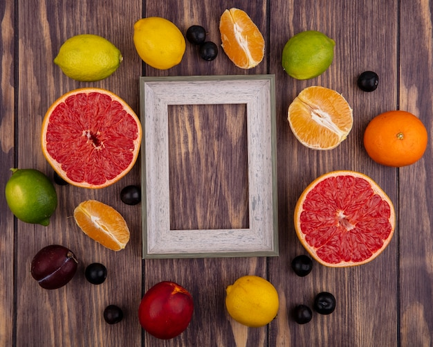 Top view  copy space gray ball frame with peach  lemons  limes  orange and half grapefruit on wood background