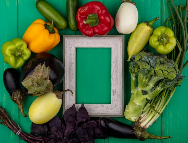 Top view  copy space gray frame with basil  bell peppers  eggplant  cucumber  green onion and broccoli on green background