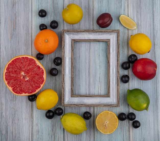 Top view  copy space gray frame with cherry plum  orange  peach  plum  lemon and lime on gray background