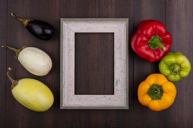 Vista dall'alto copia spazio cornice grigia con peperoni colorati melanzane bianche e nere su fondo in legno