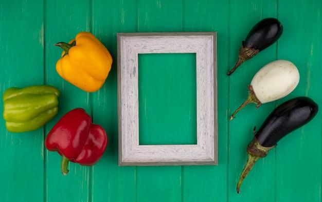 Vista dall'alto copia spazio cornice grigia con peperoni colorati con melanzane bianche e nere su sfondo verde