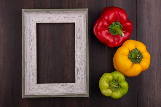Top view  copy space gray frame with colored bell peppers on wooden background