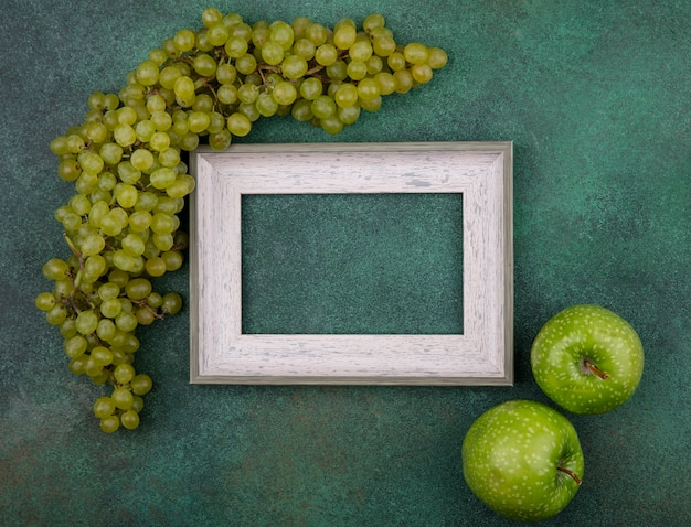 Top view  copy space gray frame with green grapes and green apples on a green background